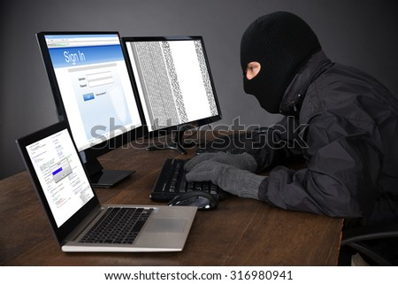 Hacker Wearing Balaclava Hacking Computers At Desk - stock photo