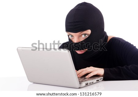 Hacker with computer wearing balaclava - stock photo