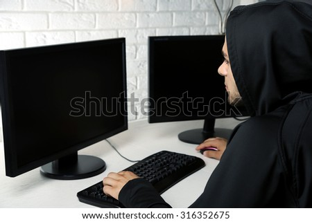 Hacker with computers in room - stock photo