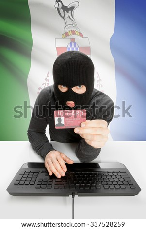 Hacker with ID card in hand and Canadian province flag on background - Yukon - stock photo