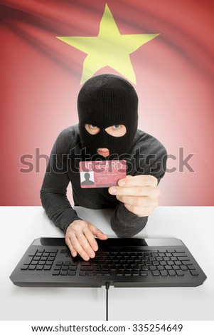 Hacker with ID card in hand and flag on background - Vietnam - stock photo