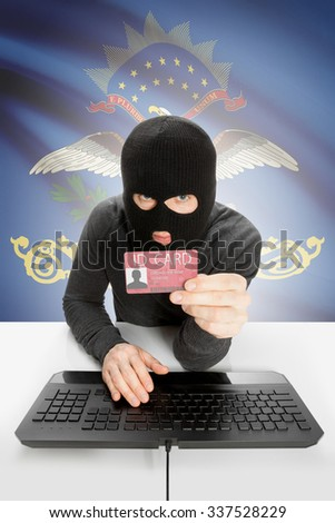 Hacker with ID card in hand and USA states flag on background - North Dakota - stock photo