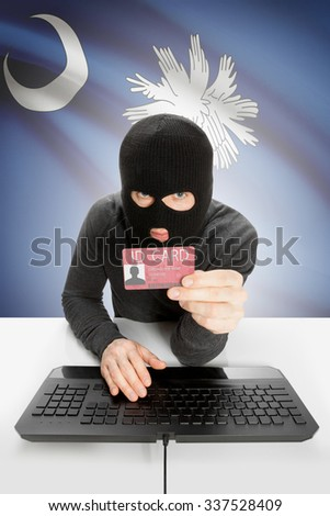 Hacker with ID card in hand and USA states flag on background - South Carolina - stock photo
