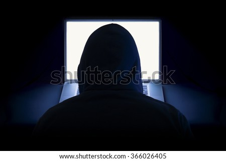 Hacker with laptop wearing hoodie - stock photo