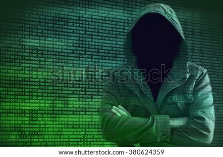 Hacker without face symbolizing anonymity of cyberspace surrounded by green binary code. Standing figure of hacker in jacket with hood. - stock photo