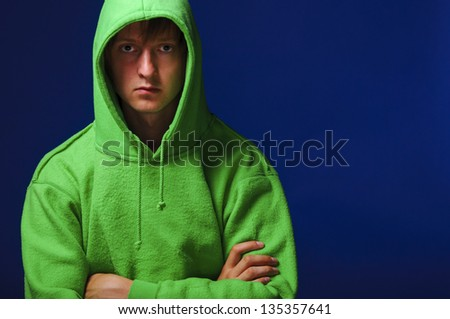 hacker. young man in green sweatshirt with turned up hood