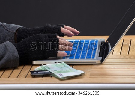 Hackers hands on keybord with stolen money and credit card - stock photo