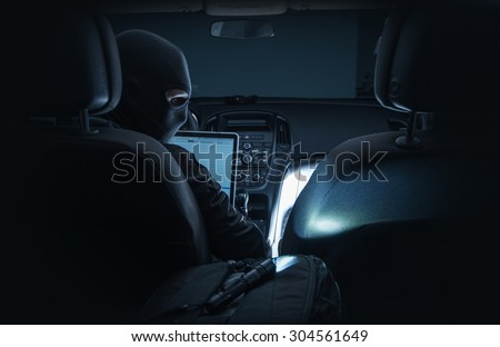 Hacking Car System. Car Hacker in Black Mask Hacking Vehicle Systems From Inside the Car Using Laptop Computer. - stock photo