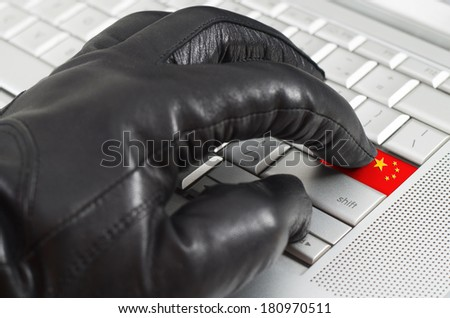 Hacking China concept with hand wearing black leather glove pressing enter key with flag overlaid - stock photo