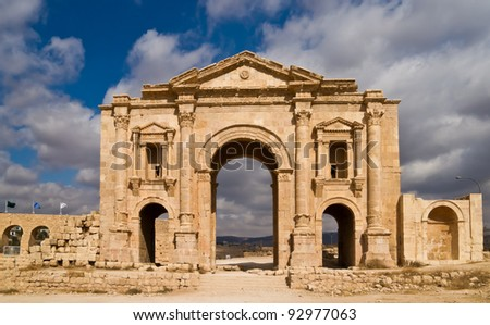 Hadrian's Arch in the ancient roman town Jerash in Jordan. Built AD 129 to honour the visiting emperor. Sunny light, nice contrast of clouds and blue sky in the background.