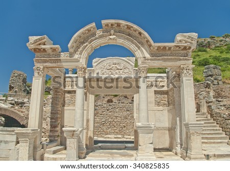 Hadrian's temple facade with green hill and clear blue sky at background in ancient city of Ephesus, Turkey - stock photo