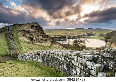 Hadrian's Wall above Cawfield Quarry / The Pennine Way walking trail joins the Roman Wall at this section,which is a UNESCO World Heritage Site - stock photo
