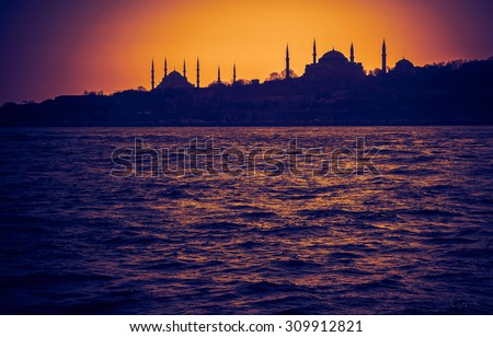 Hagia Sophia and Blue Mosque at sundown. Silhouettes of arabic architecture in sunset -  old mosques in Turkey. Panoramic view of muslim architecture landmarks with minarets in old Istanbul. - stock photo