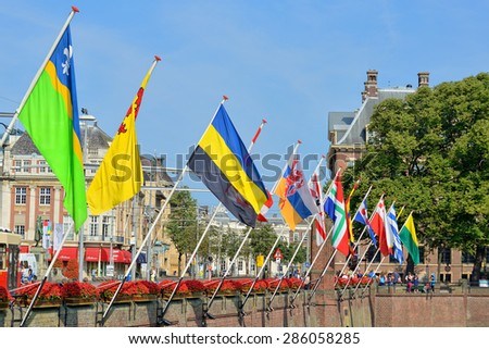 HAGUE, NETHERLANDS-AUGUST 01, 2014: Historical centre of Hague at lake Hofvijver with flags of provinces of Netherlands