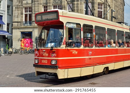 HAGUE, NETHERLANDS-AUGUST 01, 2014: Red tram moves by street in center of Hague - stock photo