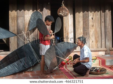 HAI DUONG, Vietnam, May 22, 2016 and her grandfather playing flute kite, summer, countryside Hai Duong, Vietnam