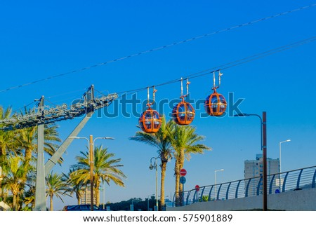 HAIFA, ISRAEL - FEBRUARY 05, 2017: View of the cable car, with palm trees and passengers, in Haifa, Israel