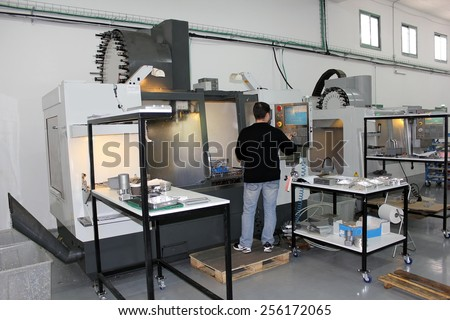 Haifa, Israel - January 18: young worker adjusts milling machine in workshop with a lathe and milling machines cnc on January 18, 2015 in Haifa, Israel - stock photo