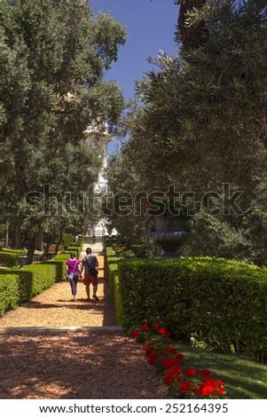 Haifa,Israel - May 24,2014:Young couple walking by the path of tropical garden in Haifa,Israel - stock photo