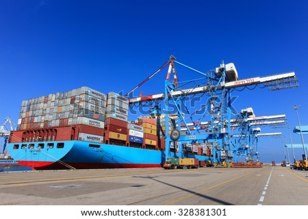 Haifa, Israel - October 15, 2015 : International Mega Container ship unloading containers on service trucks at Haifa's international port.