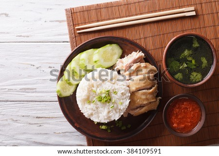 Hainanese chicken rice, chilli sauce and bouillon on the table. horizontal view from above - stock photo