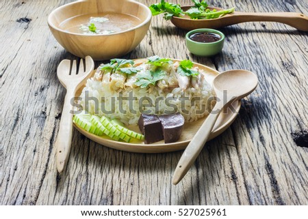 Hainanese Chicken Rice In A Plate Along With The Soup And Sauce On A Wooden Table