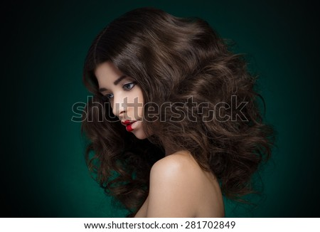 Hair and make-up topic: a very beautiful girl model with lush hair and creative make-up on blue-green background - stock photo