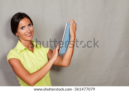 Hair back lady smiling and carrying wireless tablet while looking at camera in casual shirt on grey texture background - stock photo
