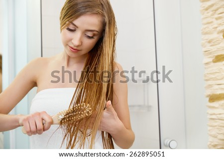 Hair. Beautiful Blond Brushing Her Wet Hair. Hair Care. Spa Beauty Model - stock photo