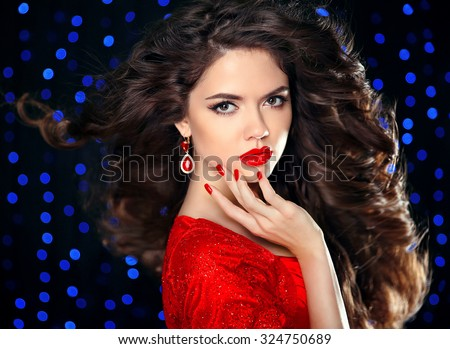 Hair. Beautiful brunette girl model with curly hairstyle, red lips makeup, manicured nails, luxury fashion earring jewelry. Elegant lady over holiday party lights background.