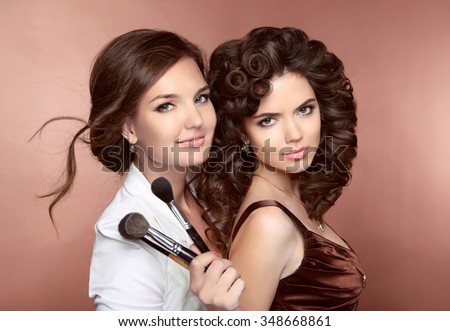 Hair. Beautiful two Brunette smiling Girls. Makeup artist with brush. Hairstyle. Attractive young women posing at camera. - stock photo