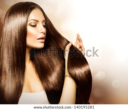 Hair. Beauty Fashion Model Woman touching her Long and Healthy Brown Hair. Beauty Brunette Girl isolated on white background. - stock photo