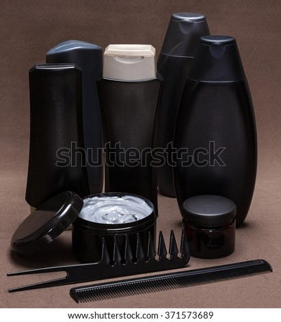 Hair care and styling products and accessories. Black and gray cosmetic containers, extra wide tooth and fine-tooth combs on brown textured surface - stock photo