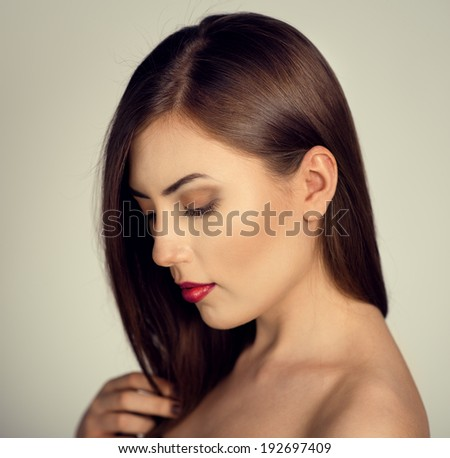 Hair coloring and care. Portrait of lovely female brunette showing her healthy long hair.