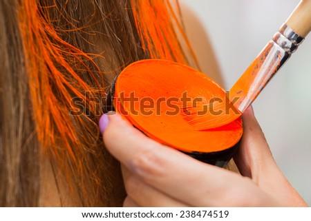 Hair coloring brush, painting hair orange. Makeup artist in the salon hair color model. Creativity, makeup, make-up, hair coloring. - stock photo