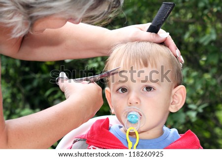 hair cutting first one-year-old child - trimming bangs - stock photo