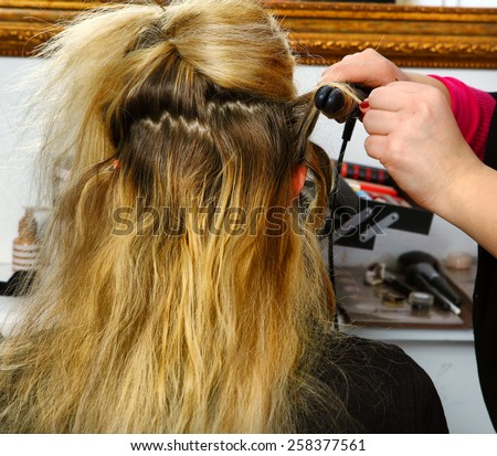 hair dresser hands make curls with curling tongs close up photo - stock photo