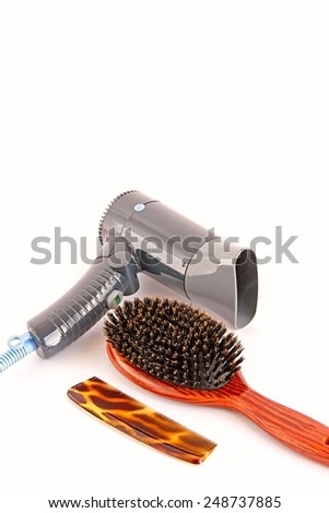 Hair dryer, boar bristle comb and plastic comb on white background. - stock photo