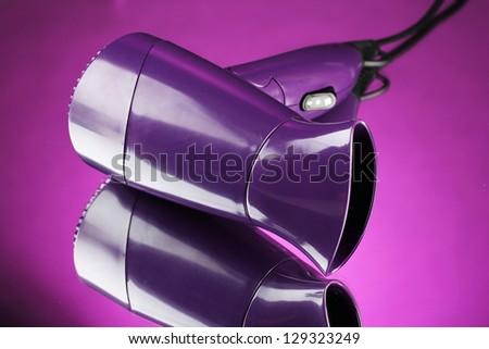 Hair dryer on purple background - stock photo