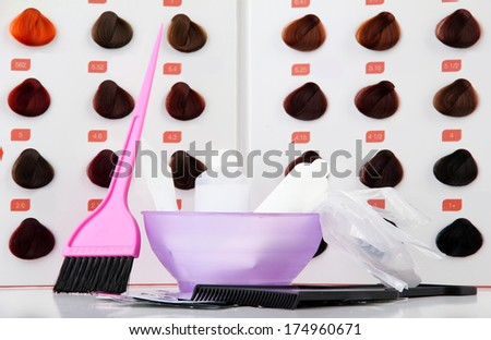 Hair dye kit on board with hair samples of different colors background - stock photo