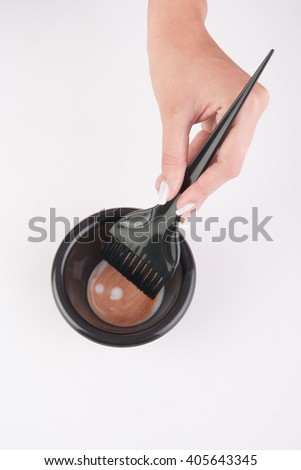 hair dye mixing bowl and brush with hand on white background - stock photo