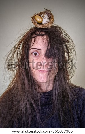 Hair like a bird's nest. Woman with messy hair and a birds nest containing eggs. Portrait. - stock photo