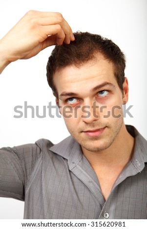 Hair loss concept - young man worried about baldness isolated on white - stock photo