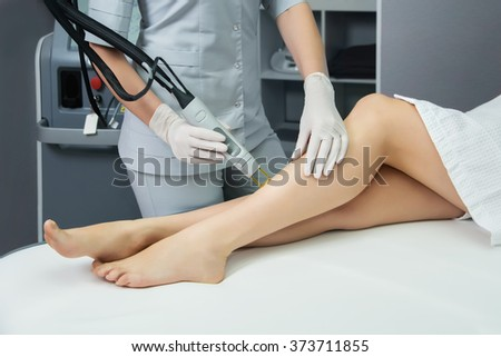 Hair removal cosmetology procedure from a therapist at cosmetic beauty spa clinic. Laser epilation and cosmetology. - stock photo
