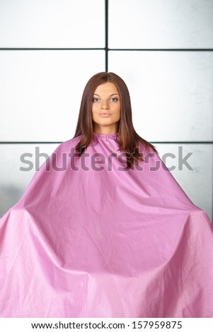 Hair salon. Young woman in hair cutting gown. - stock photo