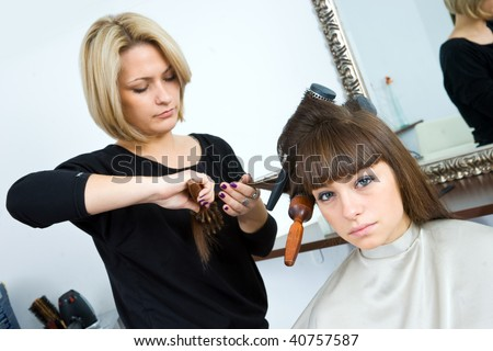 hair stylist and woman with brushes in her hair in hair salon - stock photo