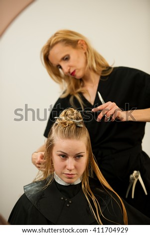 Hair stylist at work - hairdresser cutting hair to the customer before doing hairstyle in a professional salon