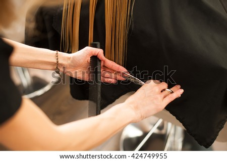 Hair stylist at work - hairdresser cutting hair to the customer before doing hairstyle in a professional salon - stock photo