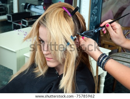 hair stylist coloring woman hair in salon