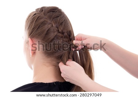 hair stylist doing plait to young woman isolated on white background